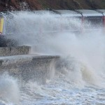 Large waves hit the seafront as a train travels along the coastal railway line at Dawlish in Devon, south west England